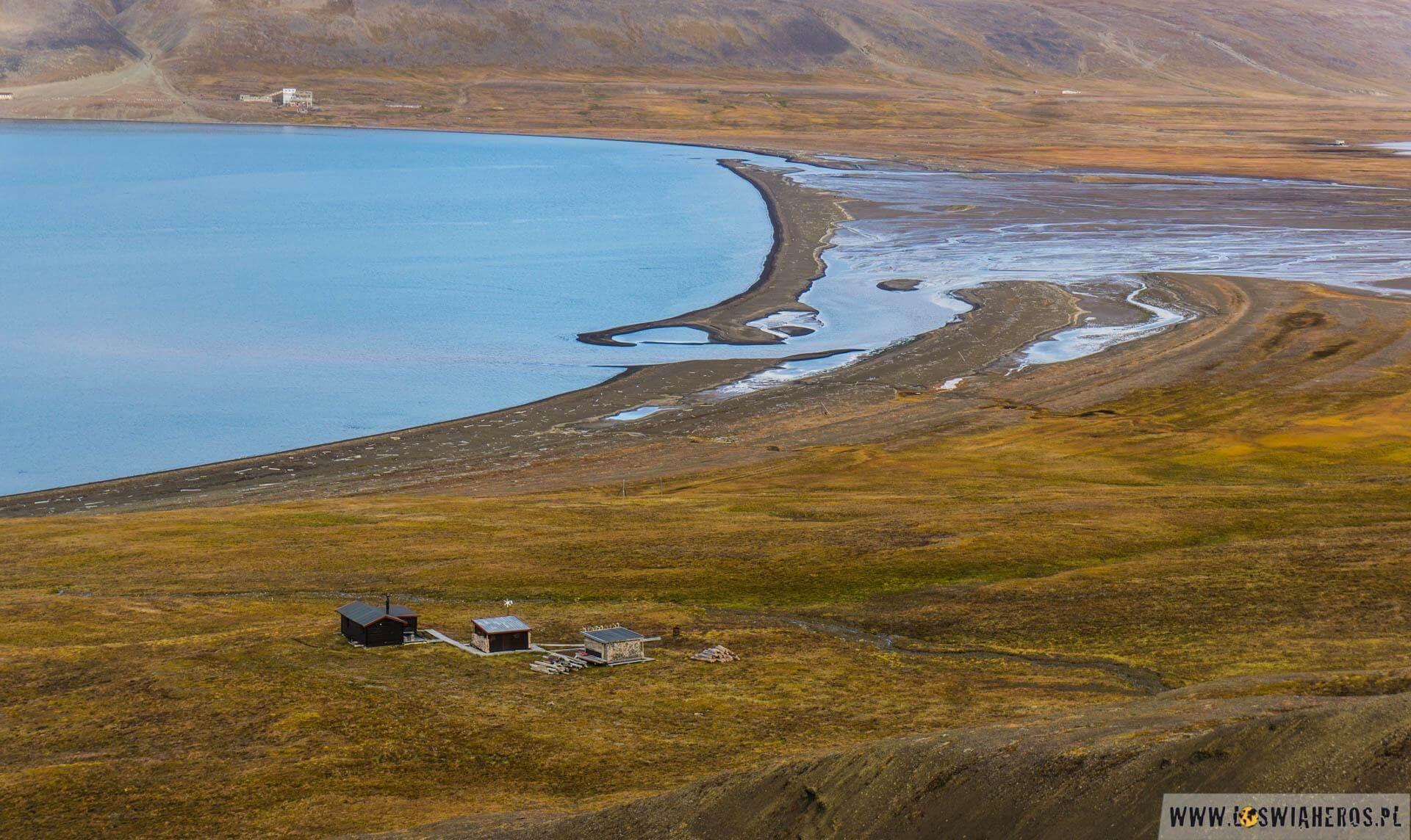 Delta arktycznej rzeczki. Przejście odcinka odtych domków udołu zdjęcia, dotych podrugiej stronie bagnistej delty zajęło nam ponad 3 godziny. Tobył jeden ztrudniejszych momentów wtym trekingu, bo ani torzeka, doprzejścia którejmożna bysię rozebrać, ani mokra tundra, poktórejtrzeba iść poprostu szybko, aby nas niezassało.
