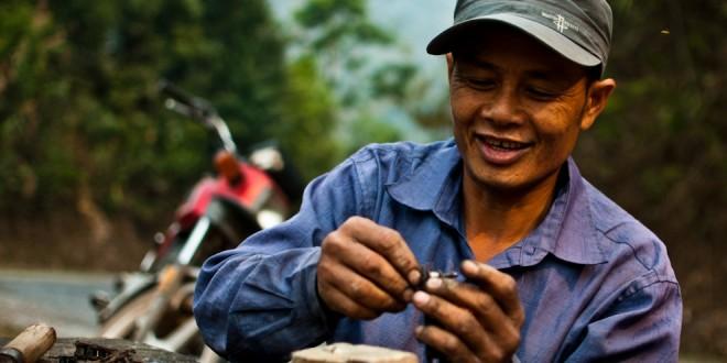 Ciągle uśmiechnięty Laotańczyk naprawia swój łańcuch... maczetą.