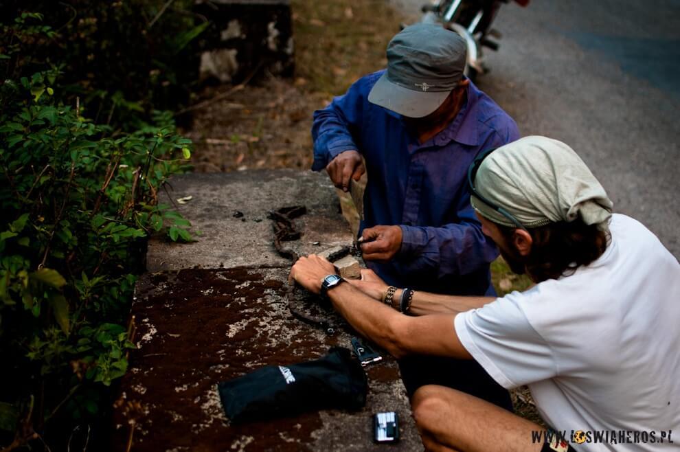 Naprawiając łańcuch w Laosie.