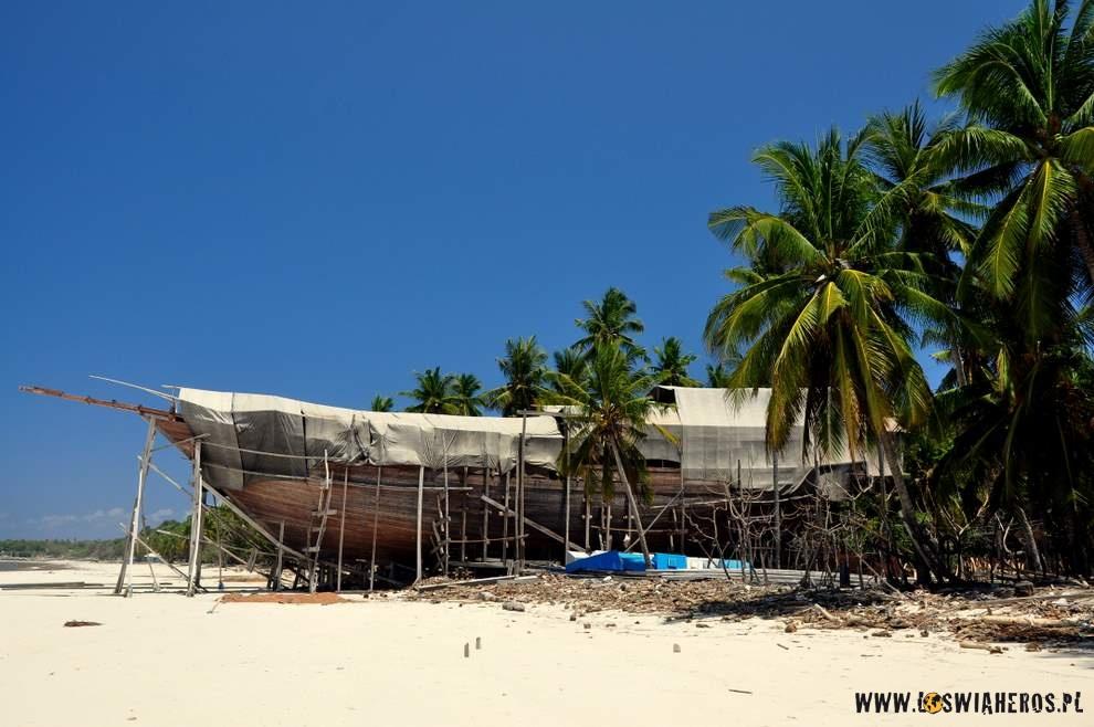 Łodzie powstają na plaży w cieniu drzew. Po skończeniu spuszczane na palach do morza.