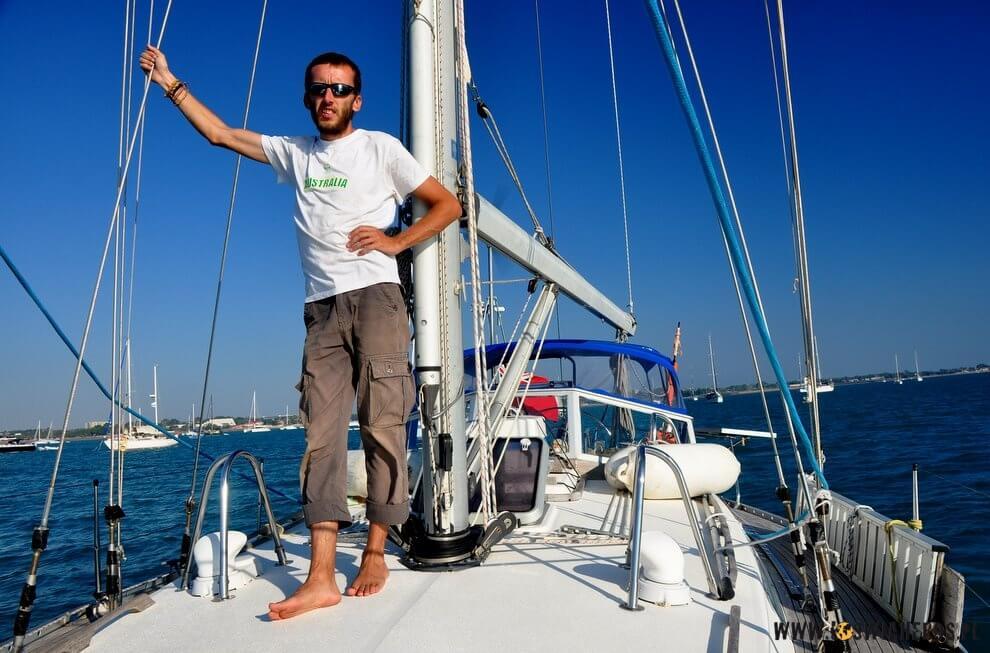 Uradowany Andrzej na pokładzie jachtu.